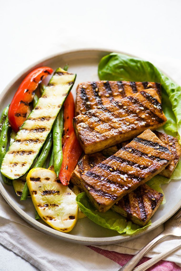 white plate with grilled zucchini, beans, bell pepper and marinated tofu