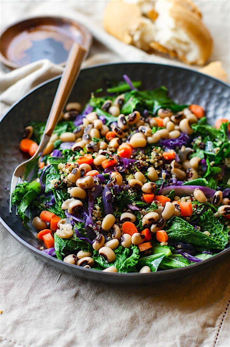 black bowl with a colorful southern vegan salad consisting of kale, red cabbage, black eyed peas, bell pepper and more plant-based food