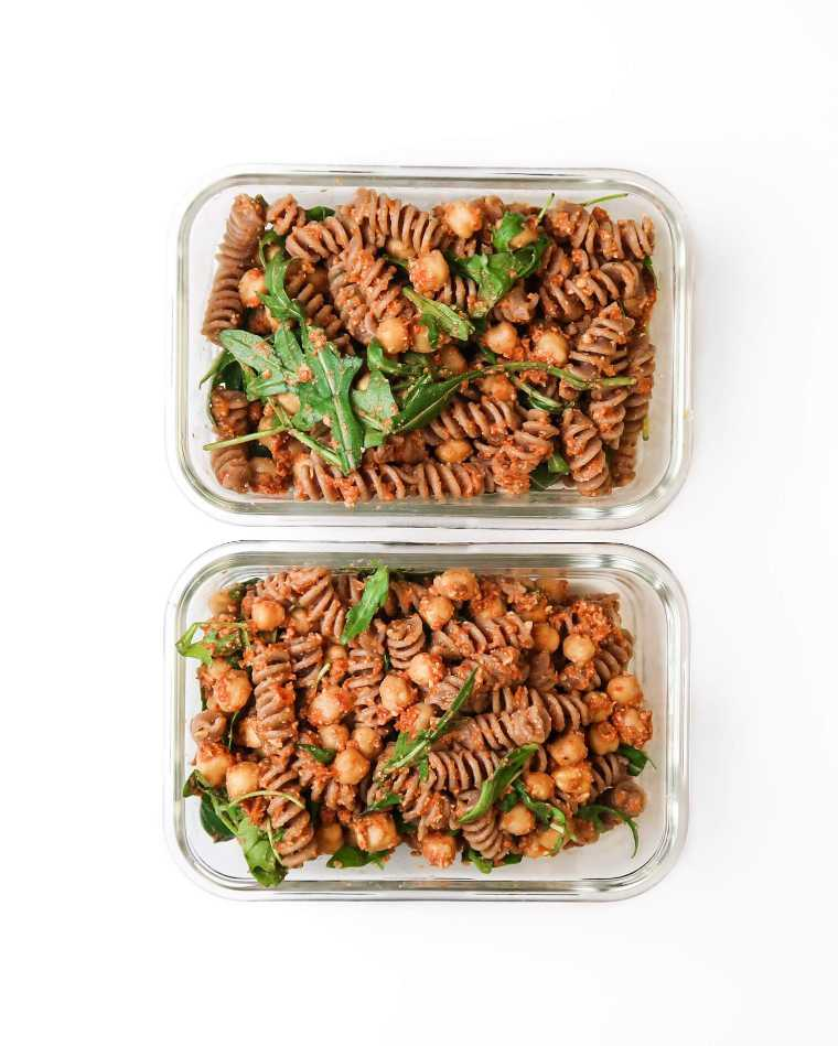 two glass containers with sundried tomato pesto pasta salad, greens and chickpeas for a portable vegan lunch