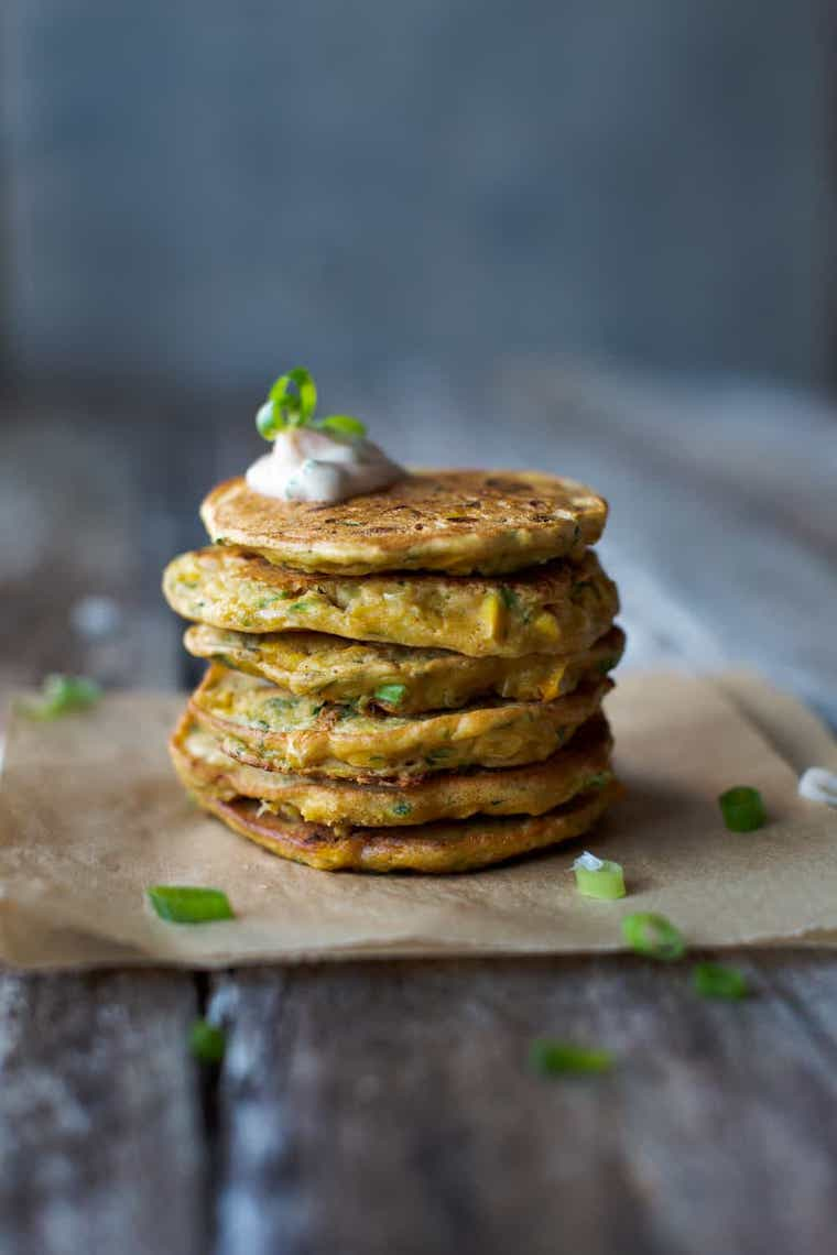 piece of parchment paper on a wooden table with six vegan corn and zucchini fritters stacked on top of each other