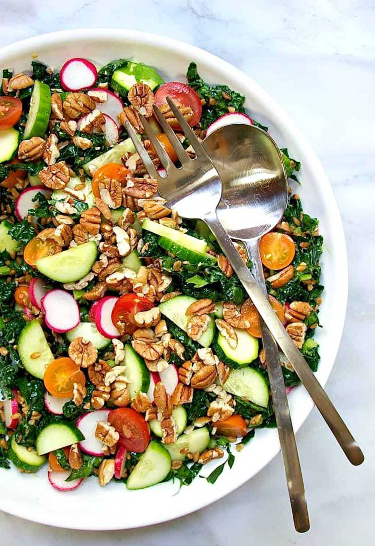 white plate with a colorful vegan farro salad with cucumber, greens, radishes, tomatoes and pecans