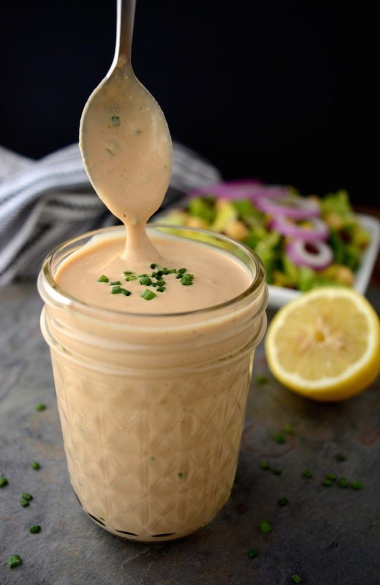 glass jar with some creamy vegan BBQ ranch dressing which is dripping from a spoon
