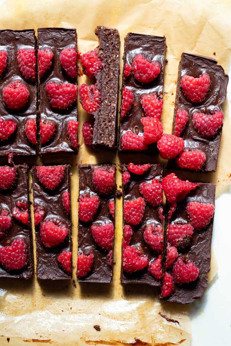 parchment paper with about a dozen of sliced no-bake vegan raspberry brownie bars