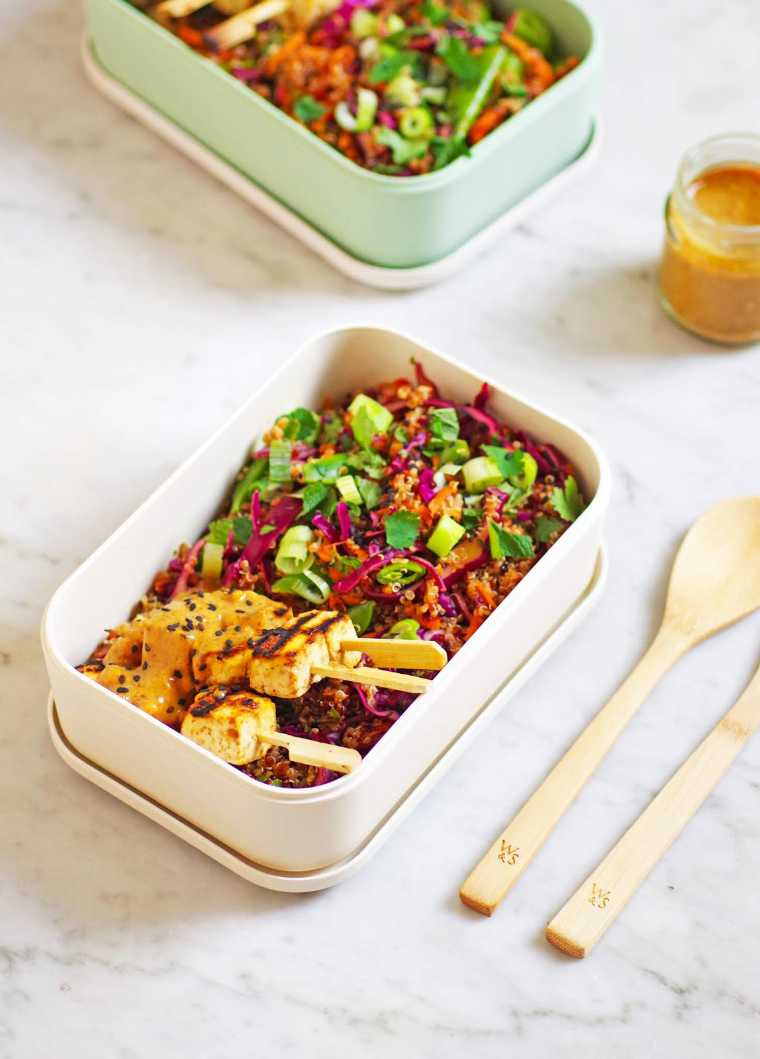 two lunchboxes filled with colorful vegan thai quinoa salad with tofu satay skewers