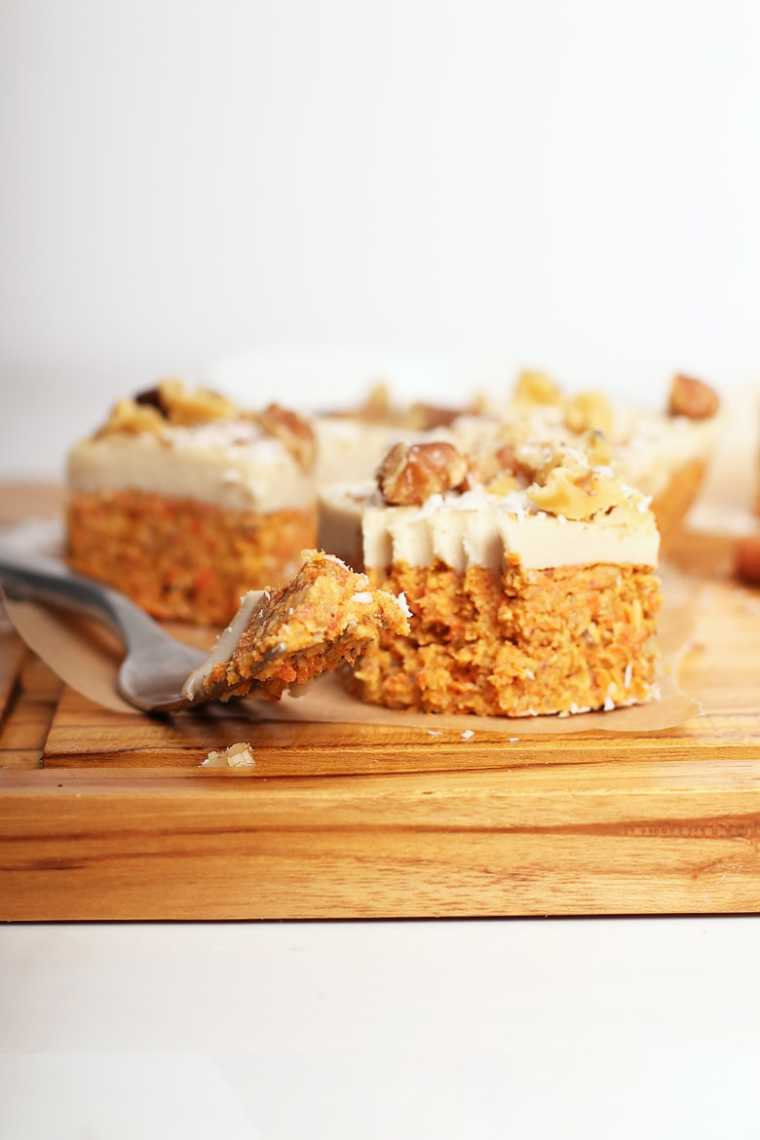 wooden chopping board with several raw vegan carrot cake squares next to a fork