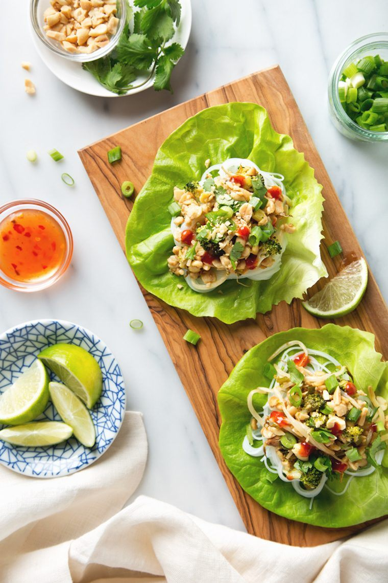 white table with wooden chopping board with open lettuce wraps that are filled with glass noodles and Thai flavored veggies