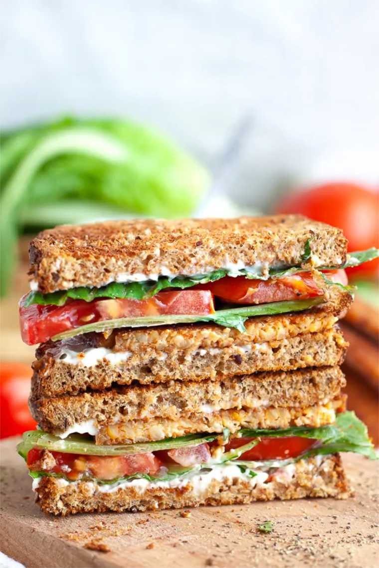 wooden chopping board with two whole grain vegan BLT sandwiches