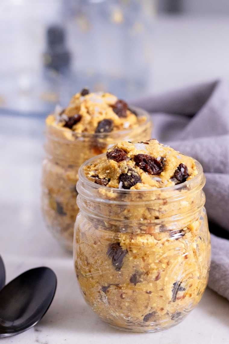 two glass jars on a table filled with Vegan Edible Cookie Dough and raisins