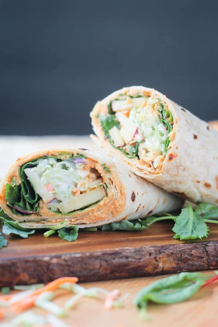 wooden chopping with two broccoli slaw veggie hummus wraps