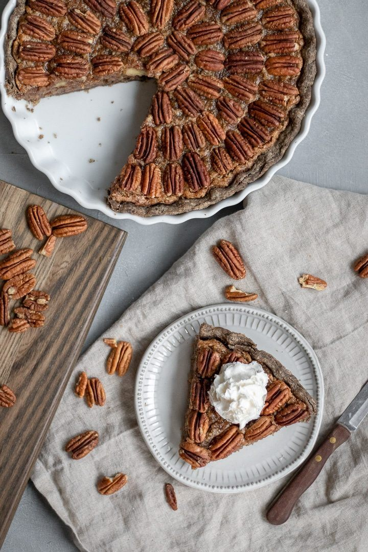 white pie form with a whole food plant based vegan pecan pie of which a piece has been cut out and placed on a small plate next to it, topped with vegan whipped yream