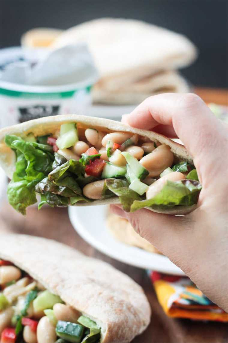 hand holding a pita pocket with salad leaves, cucumber and white beans for an easy vegan cold lunch idea