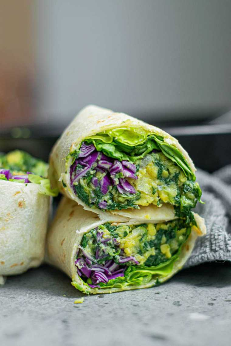 grey table with four homemade green vegan breakfast burritos for a portable lunch or snack
