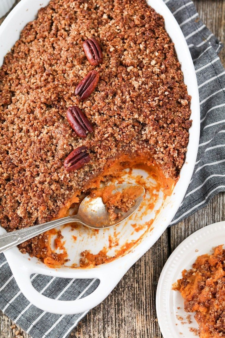 white baking dish with some vegan sweet potato casserole and pecan crumble, some taken out by a spoon