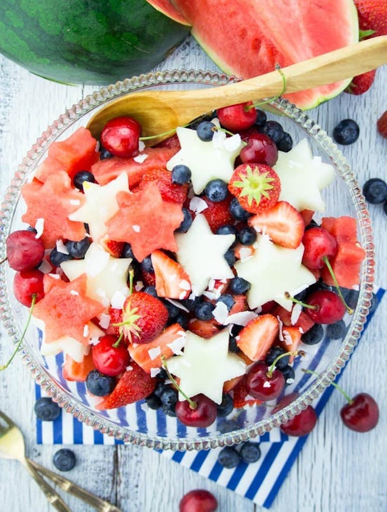 glass bowl in a table with a 4th of July fruit salad consisting of melon, berries and cherries
