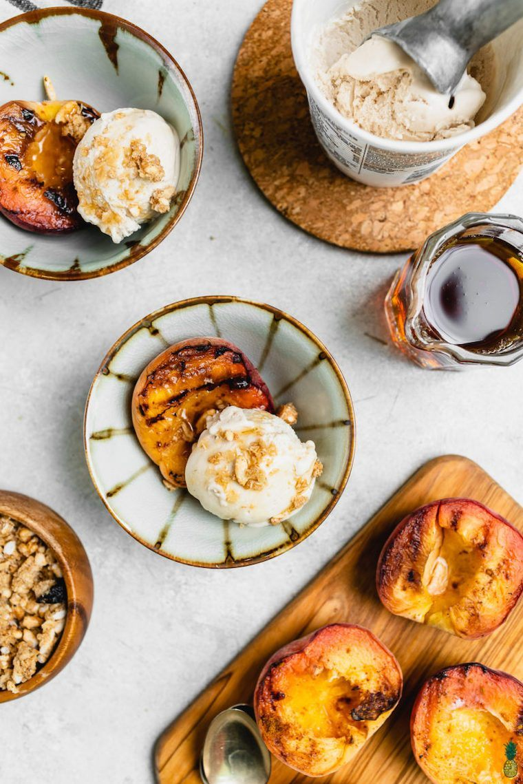 white plate with several bowls of halved grilled peaches with some creamy vegan ice cream