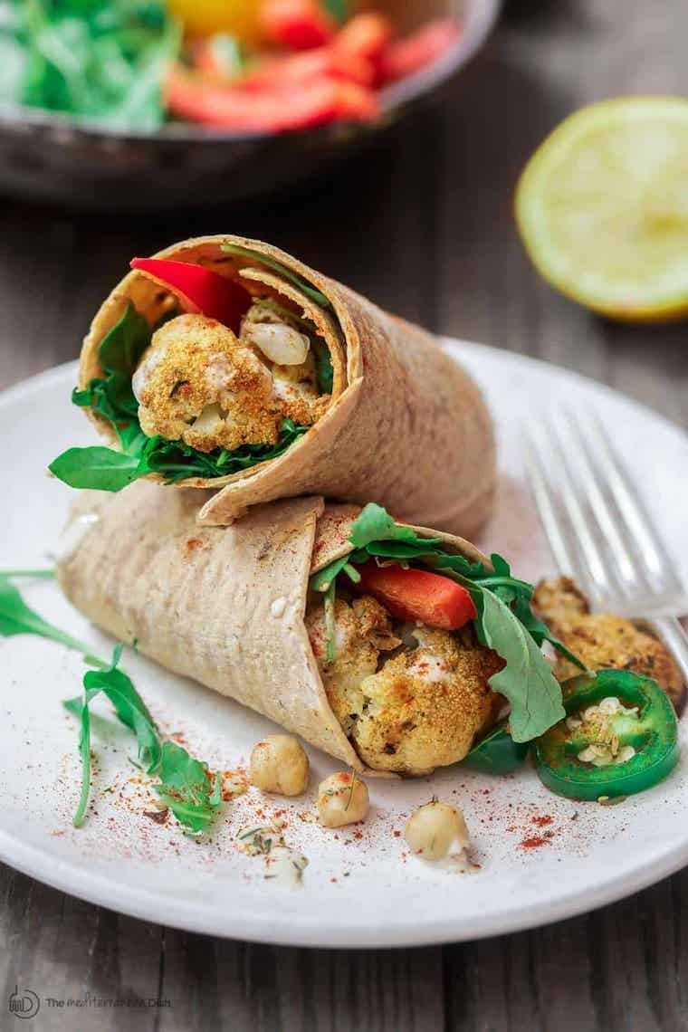 white plate with two wraps on top of each other that are filled with leafy greens, red bell pepper and cauliflower
