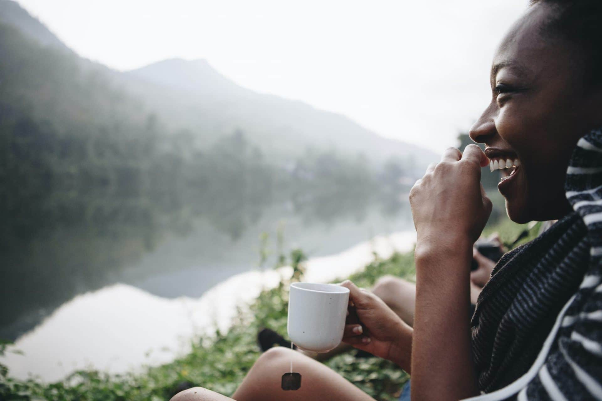 woman sitting in nature next to mountains and enjoying her tea while smiling