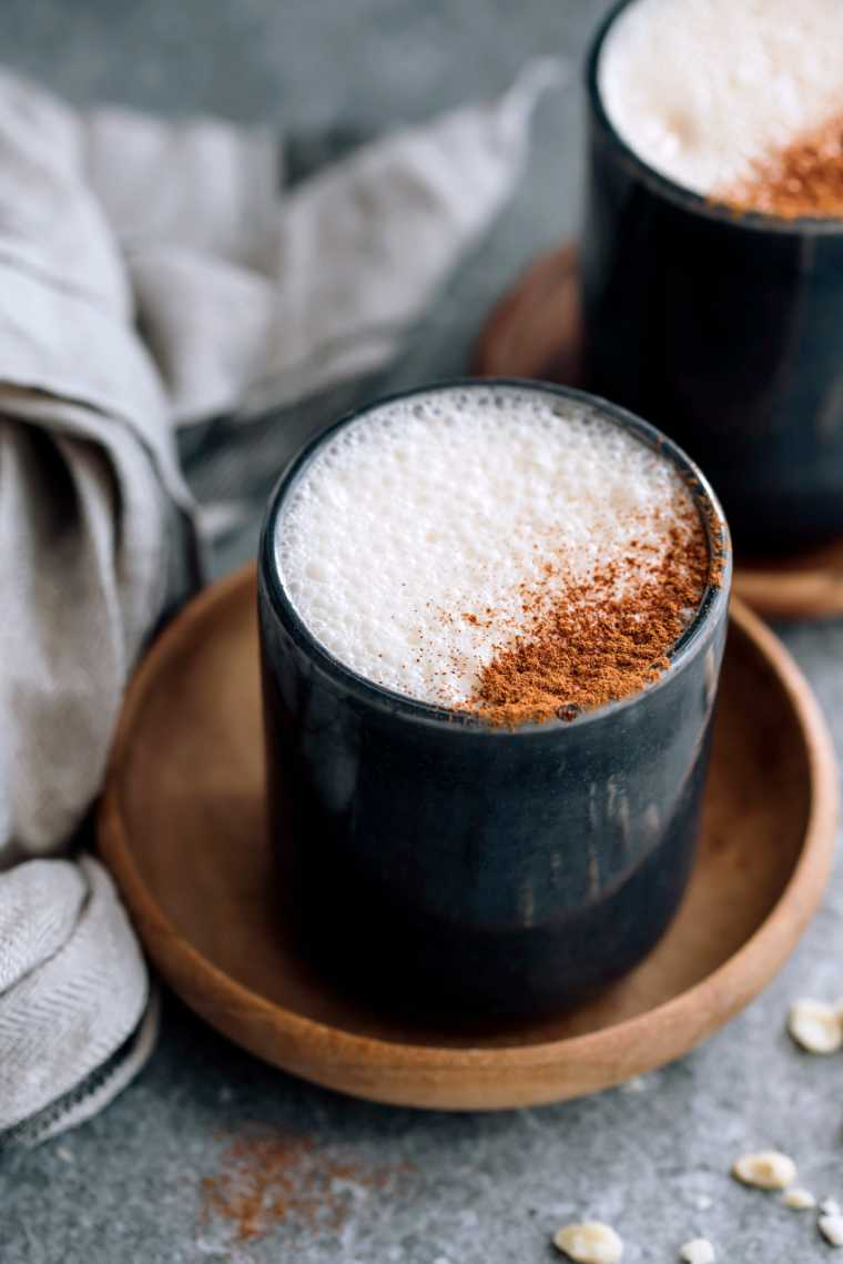 two cups of frothy vegan latte topped with cinnamon next to a linen towel