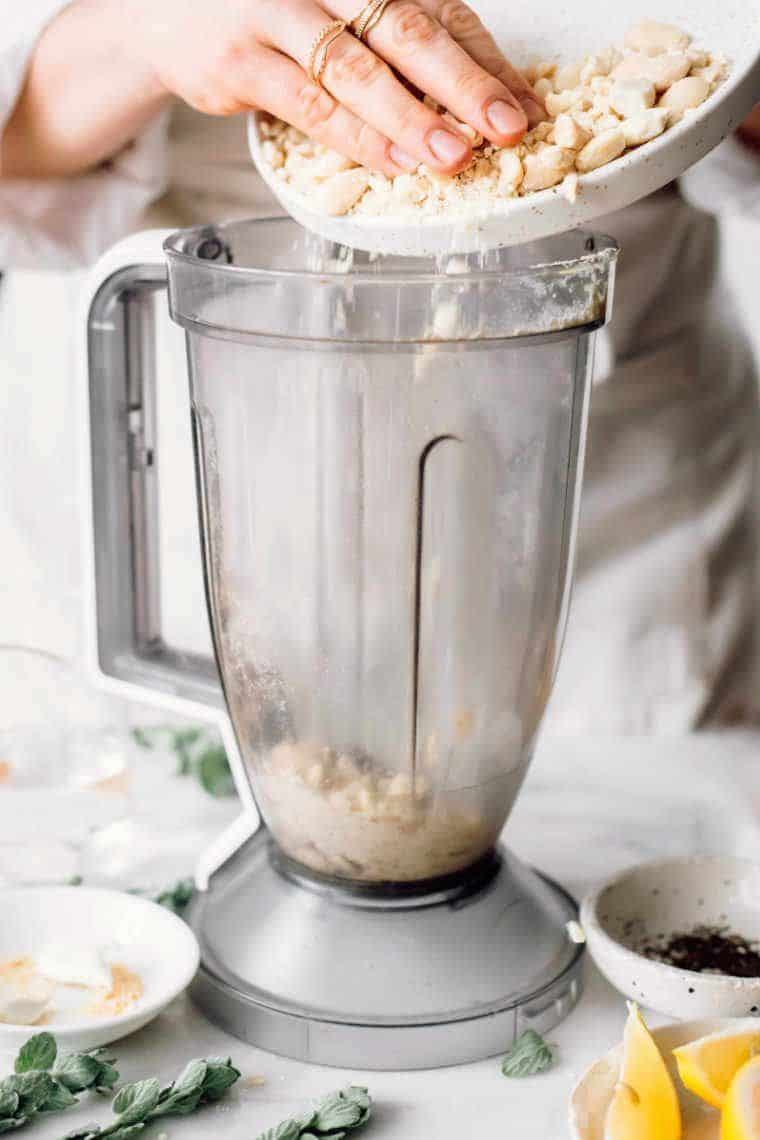 woman in white apron standing next to a blender jar and putting almonds into it