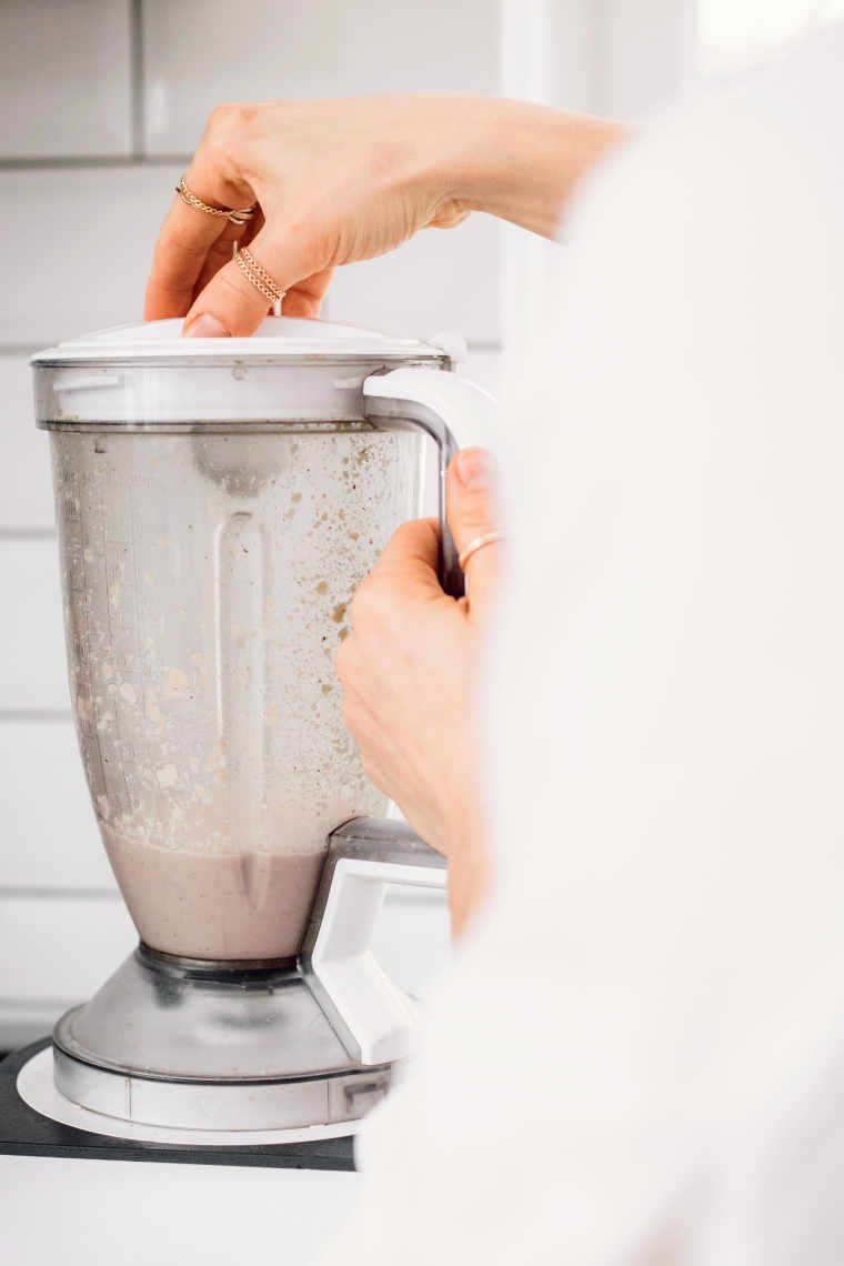 woman standing next to a high speed blender and blending ingredients together to make almond ricotta
