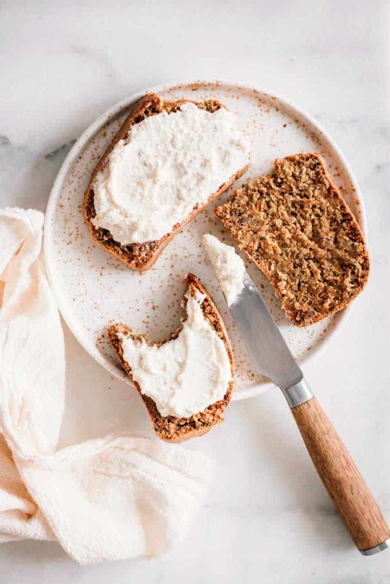 white plate with a few pieces of bread with almond ricotta next to a knife