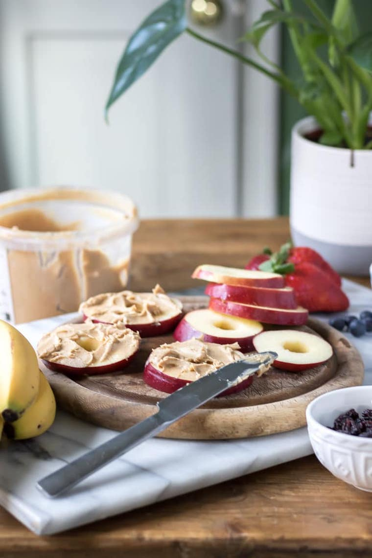 wooden table with a jar of peanut butter and a chopping board with apple slices that are being spread with peanut butter