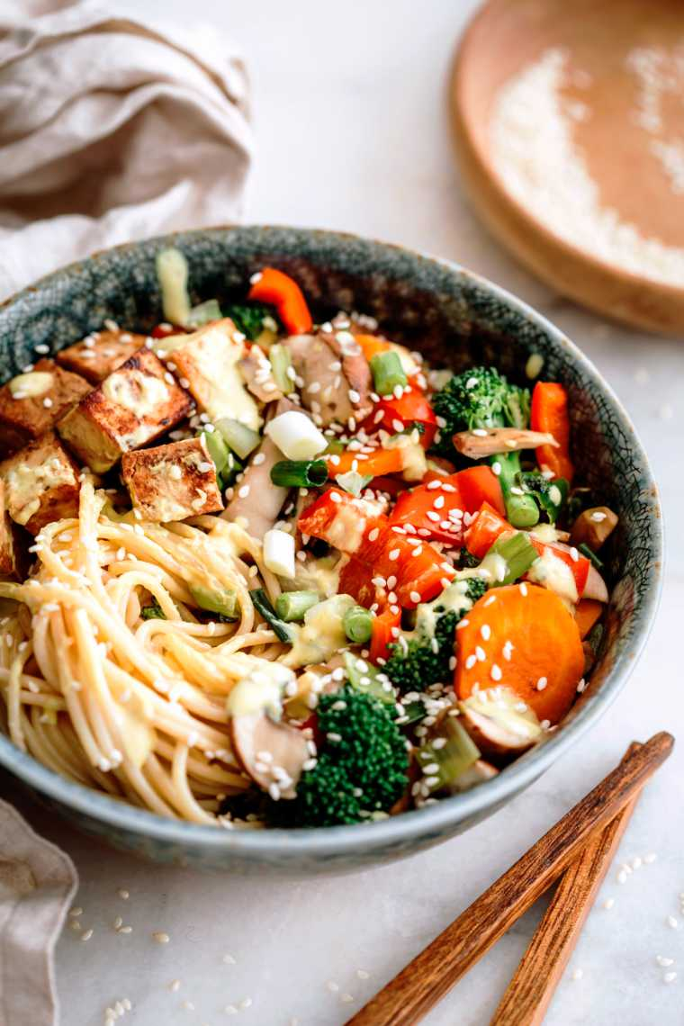 close up of a large bowl with cooked noodles and different Asian veggies, such as carrot, bell pepper and broccoli as well as some marinated tofu next to two chopsticks