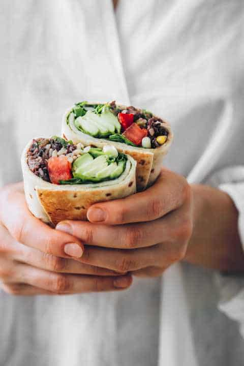 woman in white shirt holding two homemade vegan bean burritos in her hands