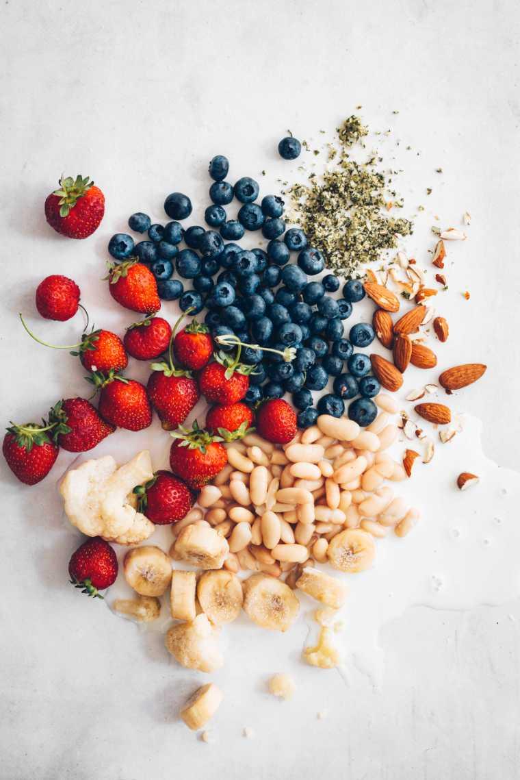 white table with strawberries, blueberries, white beans, hemp seeds, banana, almonds and cauliflower