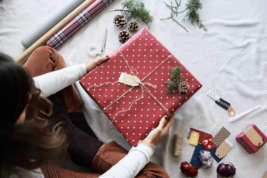 Overhead of female holding beautiful wrapped gift diy at home for christmas