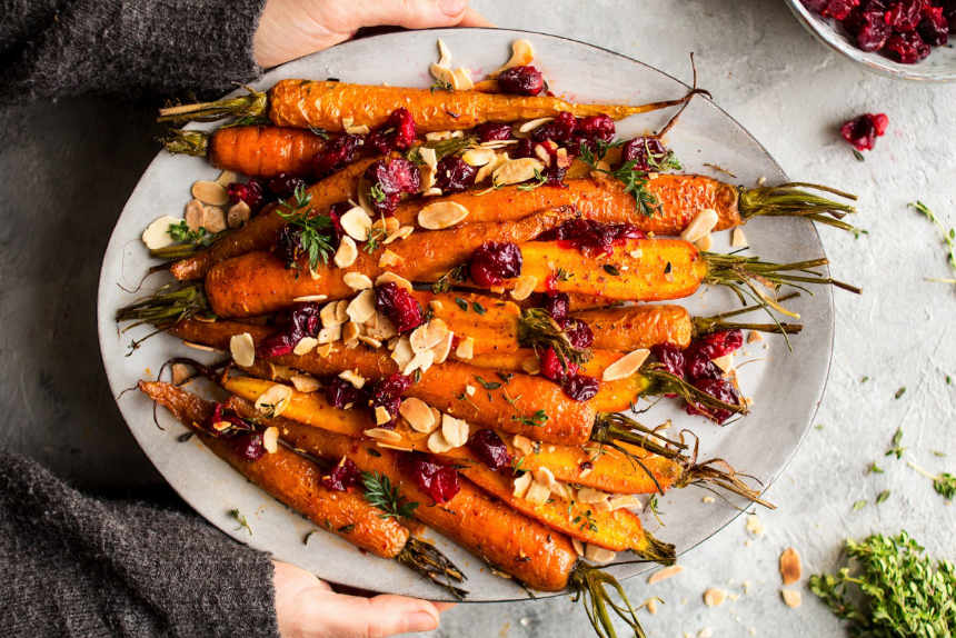 white plate of roasted carrots with cranberries and almonds on a white table