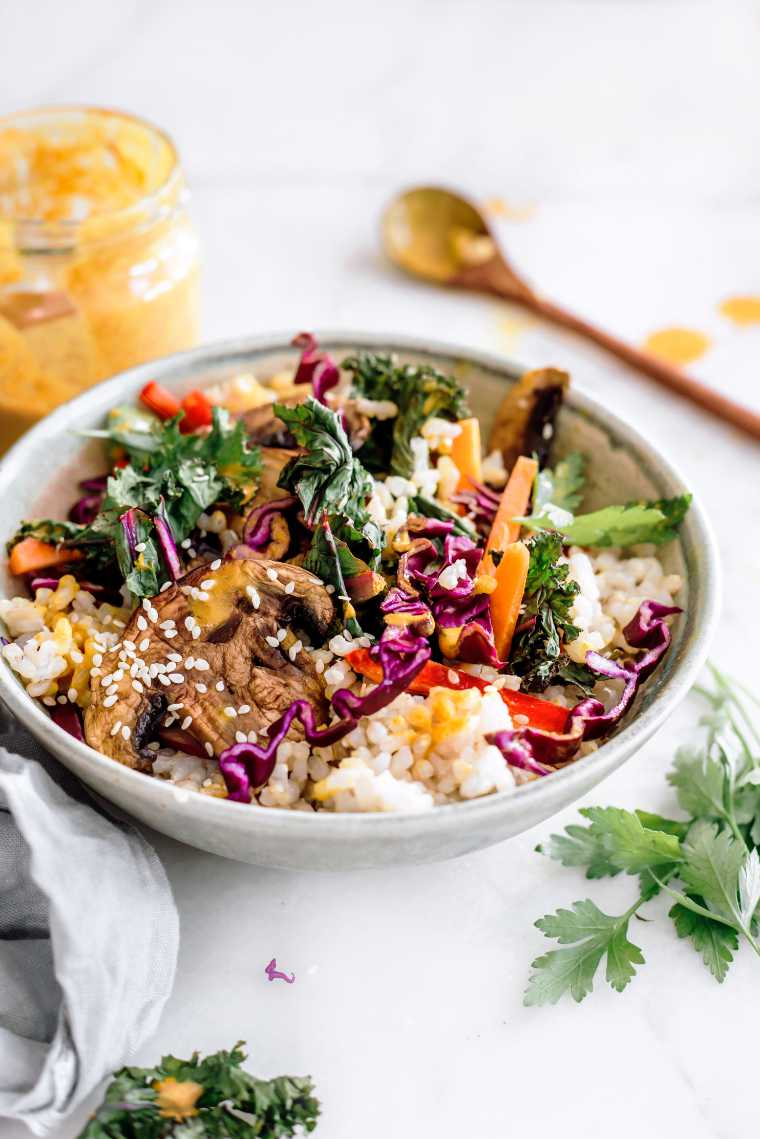 close up of a white bowl containing rice, mushrooms, red cabbage, sliced carrot, bell pepper and kale next to a creamy miso dressing