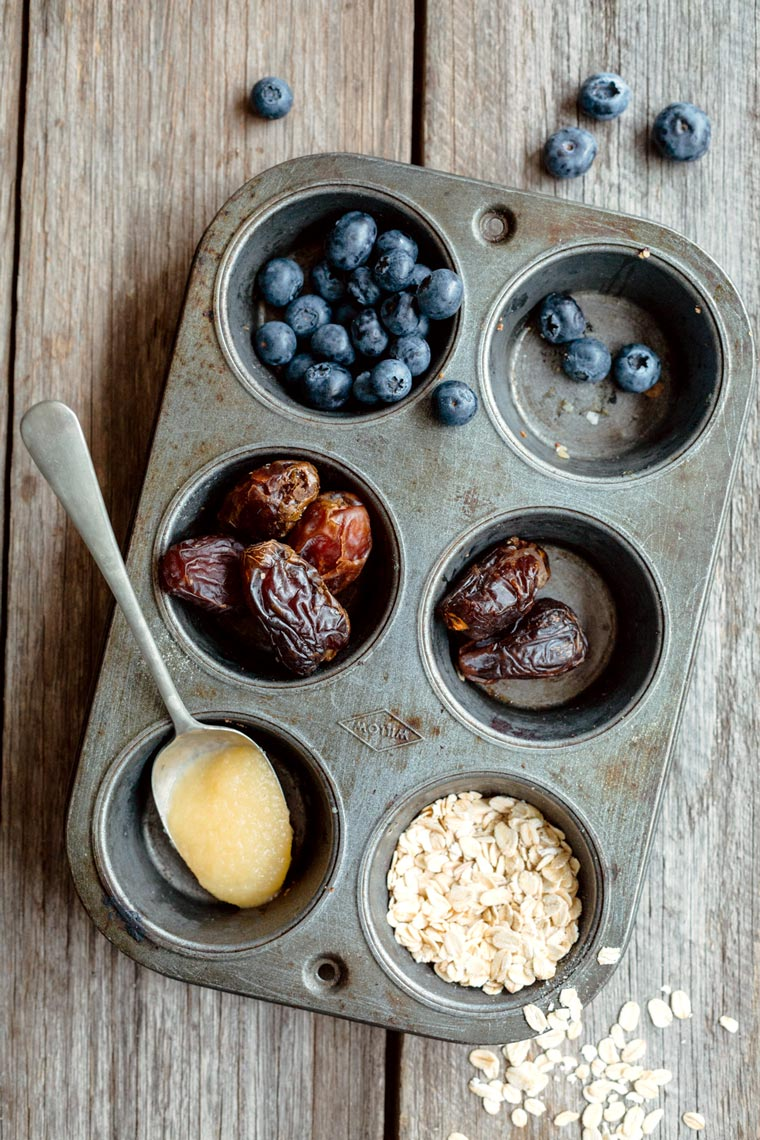 top view of a muffin tin with different ingredients that are used to make gluten-free blueberry muffins, such as dates, applesauce and oats