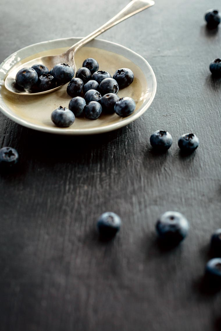dark table with a shallow ceramic bowl carrying a handful of fresh blueberries