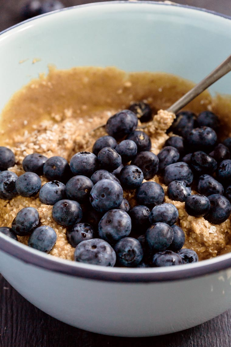 white bowl with mixed gluten-free batter for muffins topped with fresh blueberries