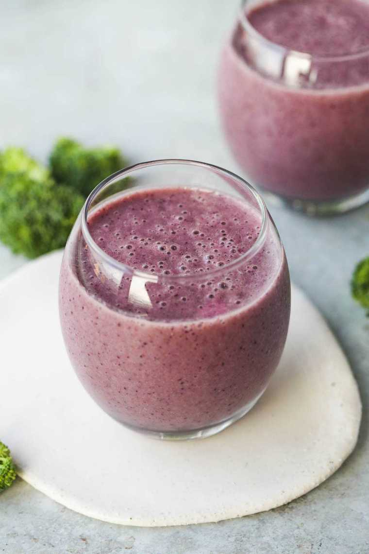 two glasses of purple blueberry broccoli smoothie next to some broccoli florets