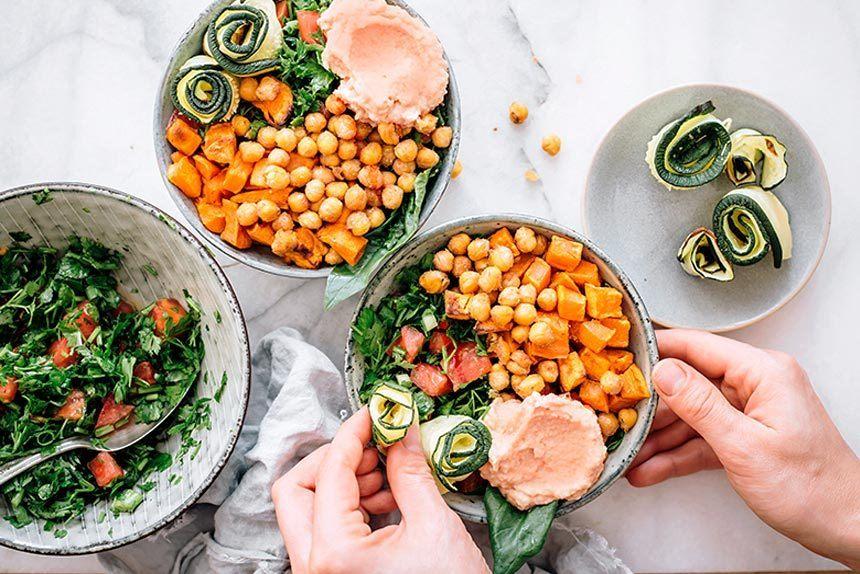 two hands placing zucchini rolls in a bowl with sweet potato, chickpeas, greens and hummus