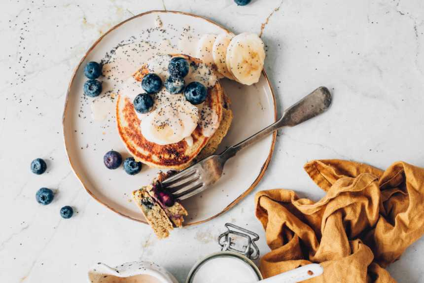 vegan pancakes topped with blueberries and banana on a white plate