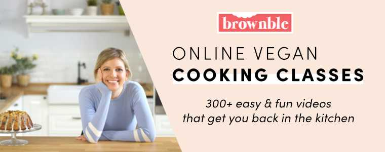 smiling blonde woman leaning on the wooden counter in her kitchen next to a cake with the words online vegan cooking classes and brownble on the right side