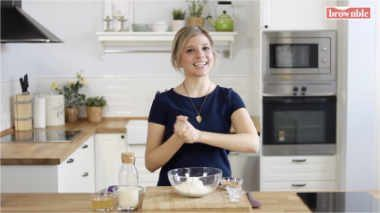 Blonde woman wearing a blue shirt standing in a white modern kitchen in front of a glass bowl with some flour