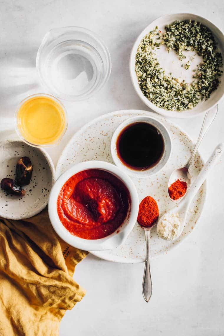 top view of table with a bowl of hemp seeds, two dates, a bowl of soy sauce and tomato paste