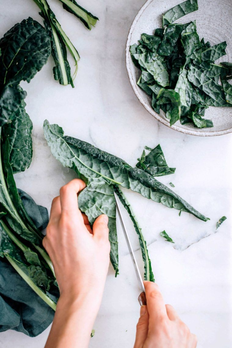 woman cutting fresh kale leaves with a knife on a marble surface