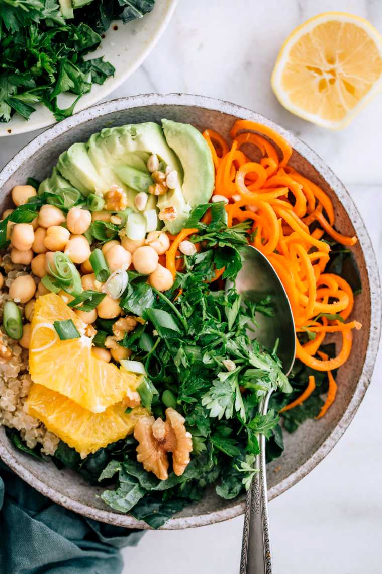marble table with a bowl of spiralized carrots, quinoa, chickpeas, chopped greens and avocado