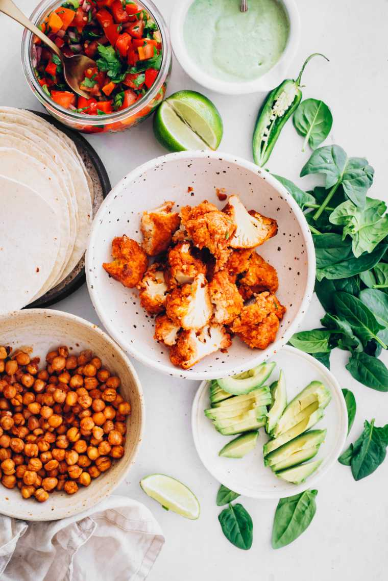 white table with salsa, roasted chickpeas, buffalo cauliflower bites, avocado and fresh spinach