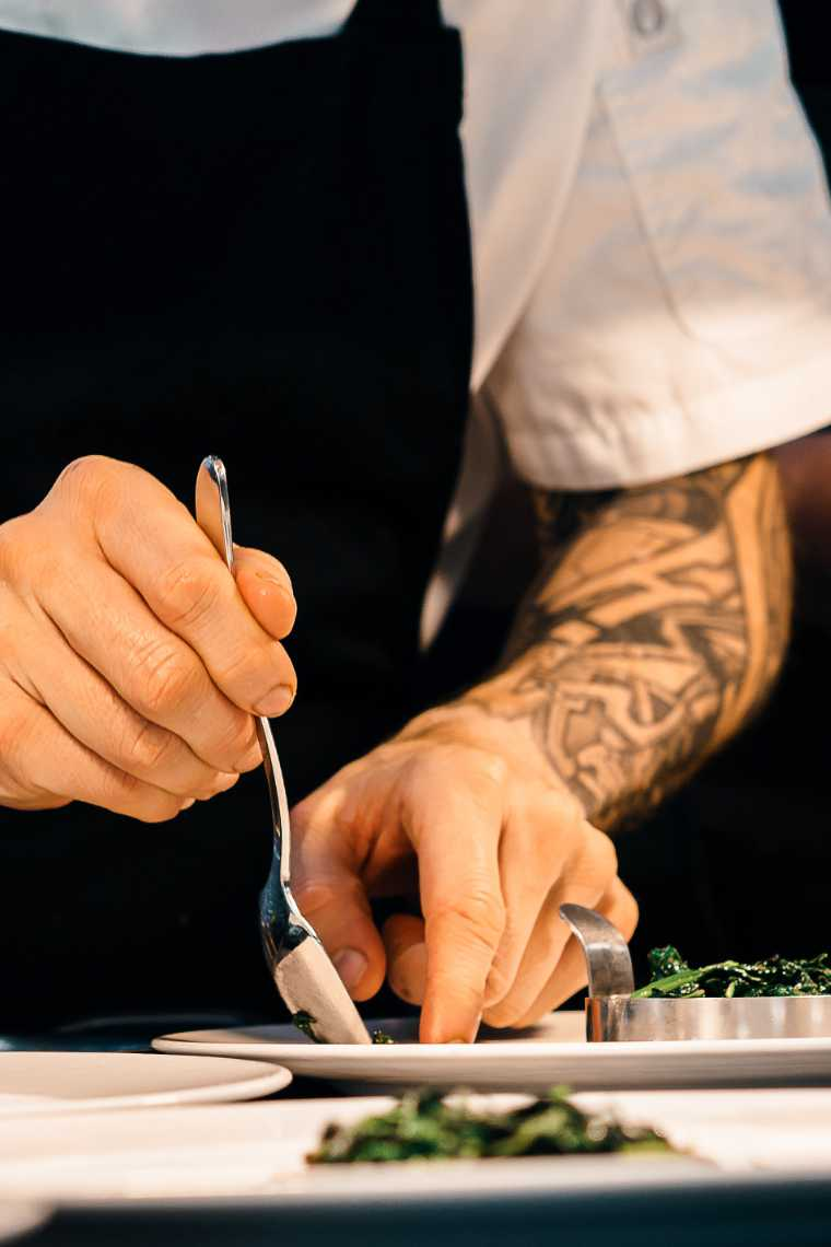 Closeup of male chef with tattoos arranging green vegetables on a plate