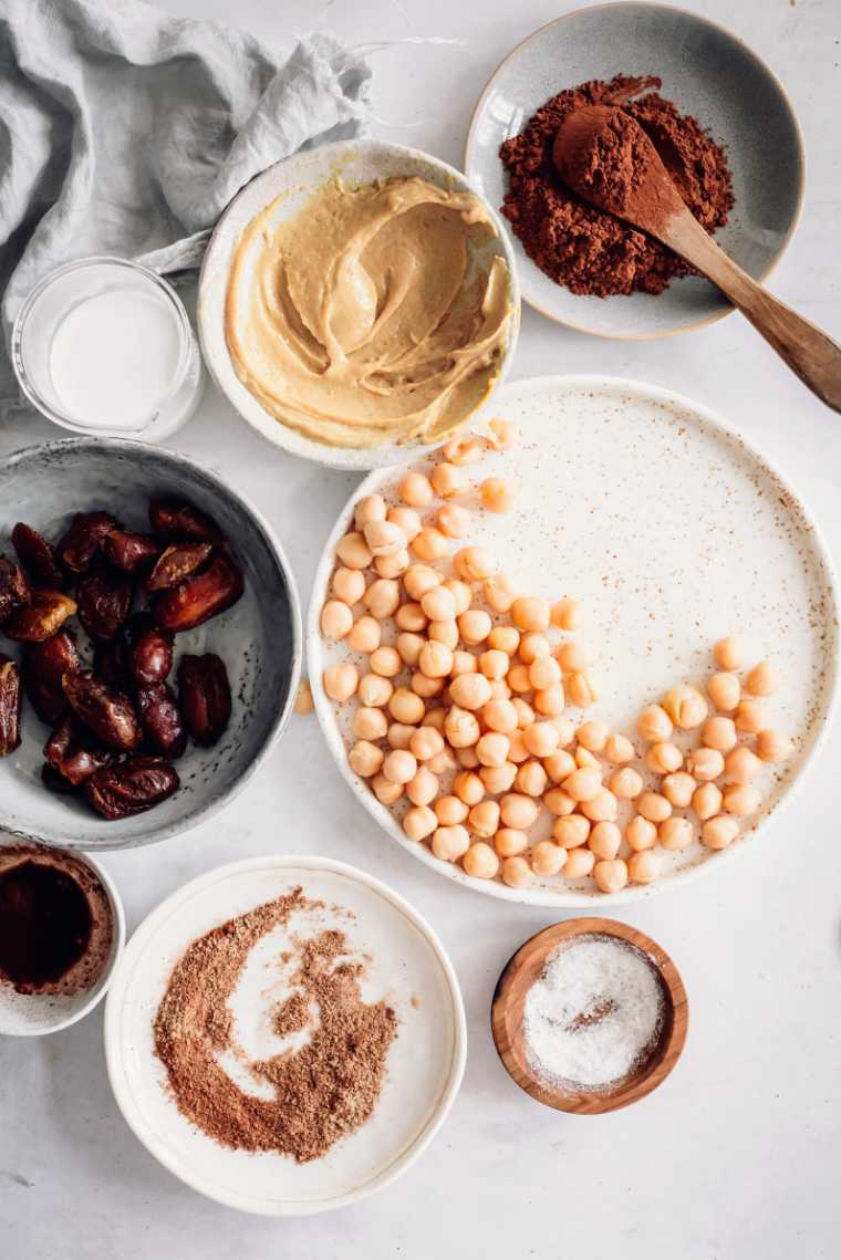 white table with different small bowls containing chickpeas, dates, peanut butter. cocoa powder and some spices