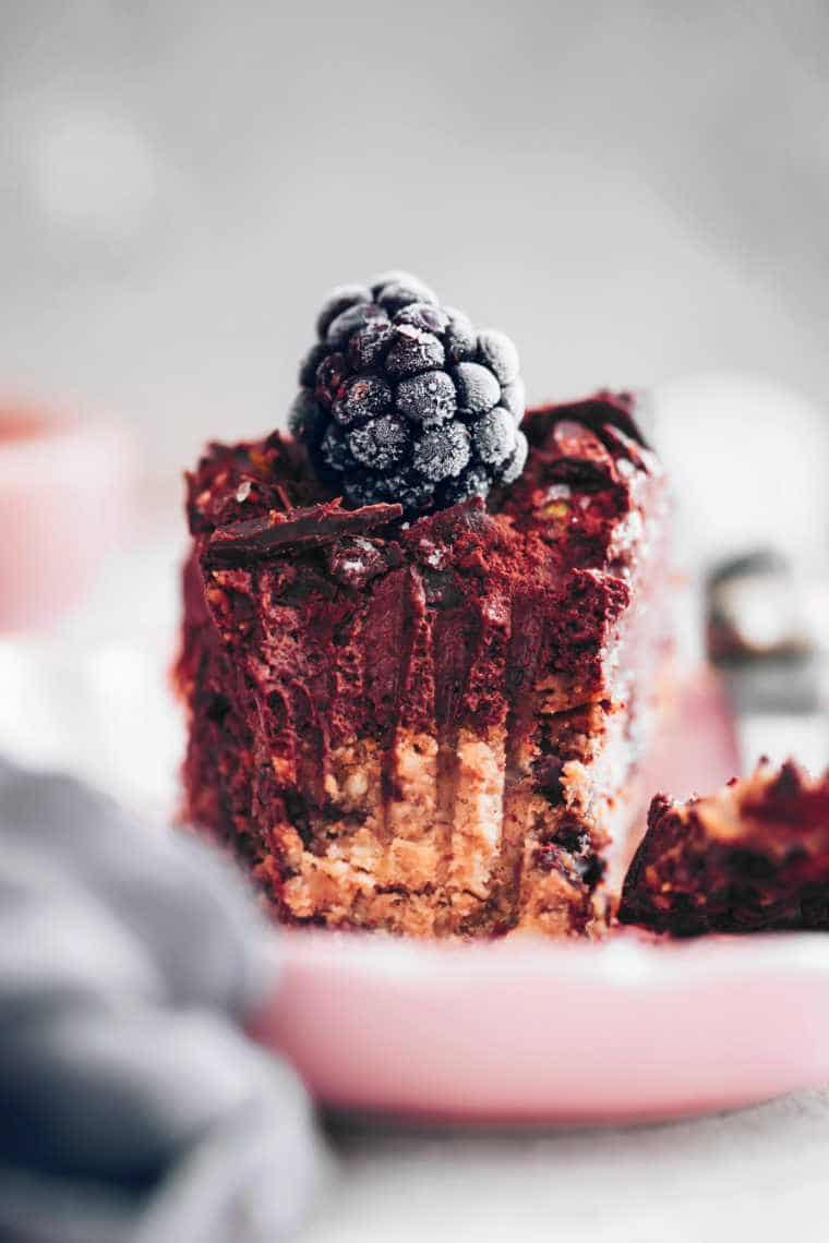 front view of a half eaten chocolate mousse cake slice with a frozen blackberry