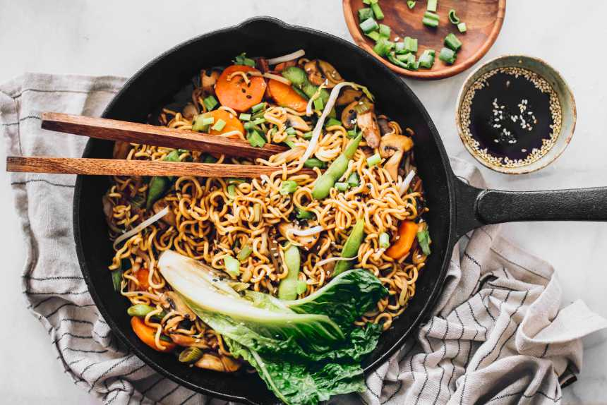 white table with a black pan filled with homemade vegan chow mein noodles