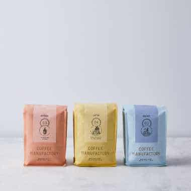 three colorful packaged coffee samplers in red, yellow and blue next to each other