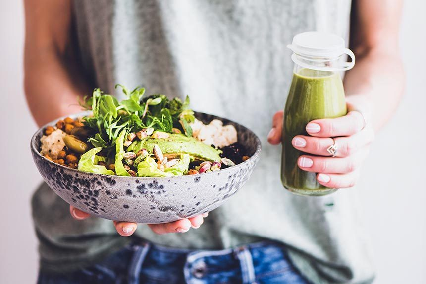 woman in green shirt and jeans holding a grey speckled bowl of green vegetables and beans in one hand and a green smoothie in the other